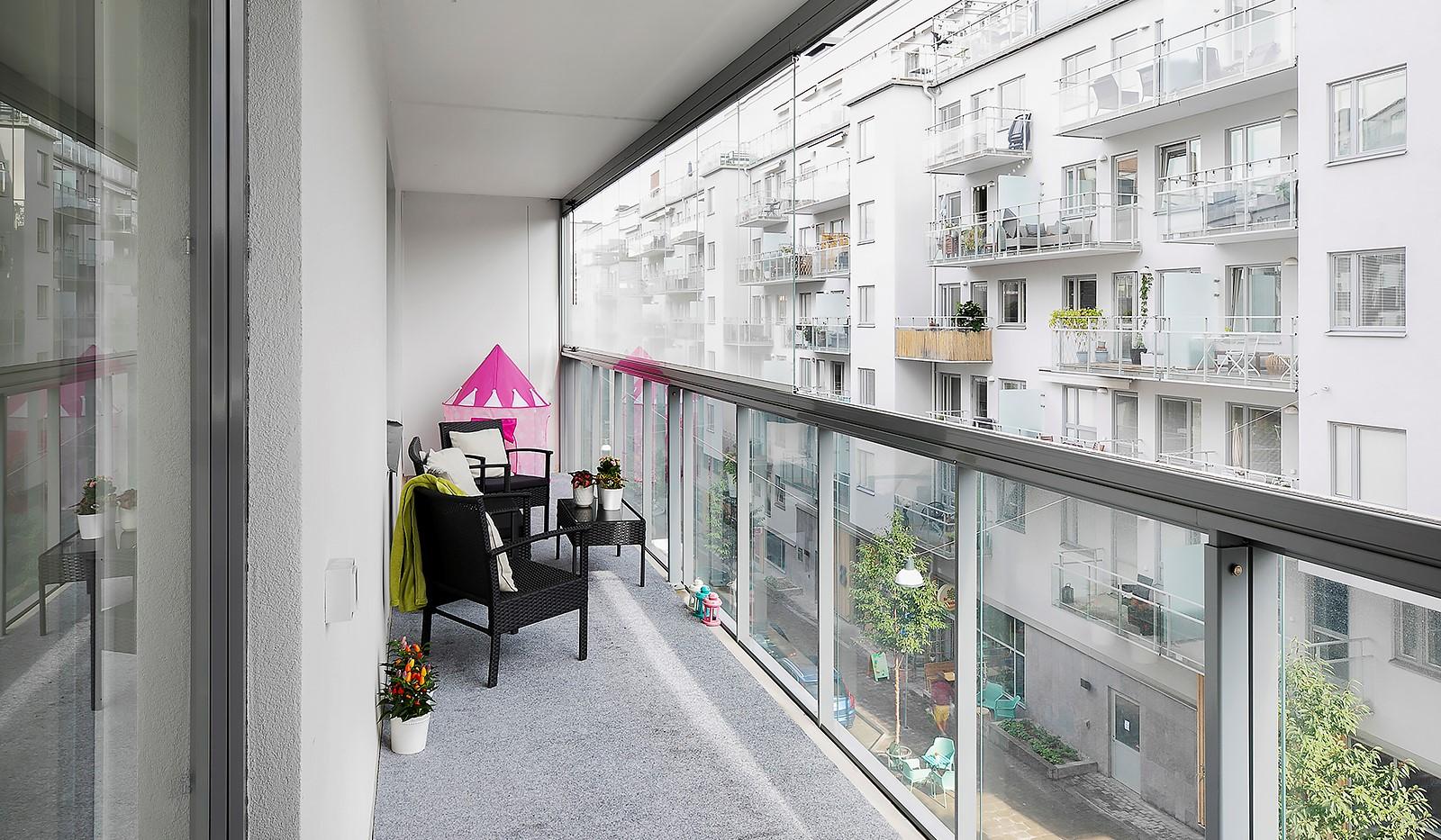 Hammarby Allé 15, vån 5 - Balkongen är inglasad med en smart dragspelsmetod där glasskivorna lätt kan dras fram och tillbaka